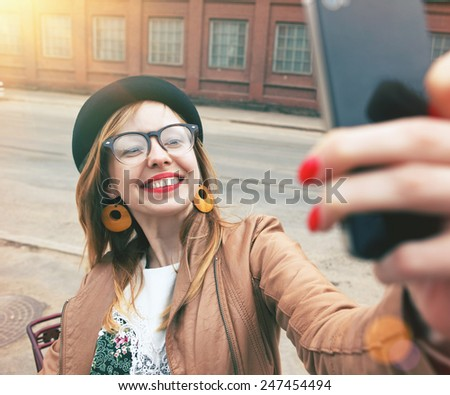 City lifestyle stylish hipster girl using a smartphone taking photo selfie with camera in a street - stock photo