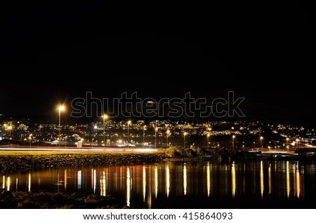 city lights in winter night with reflection on fjord surface