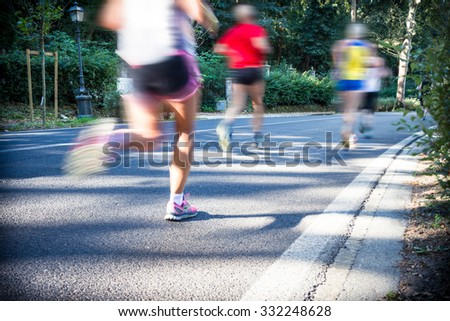 City marathon runners. Long exposure with motion blurred effect. Selective focus on the foreground. Slight vignetting effect.  - stock photo