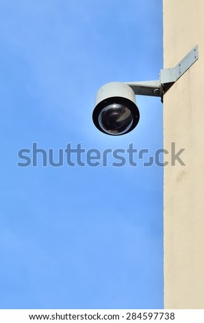City monitoring. Security camera on building against a blue sky background.