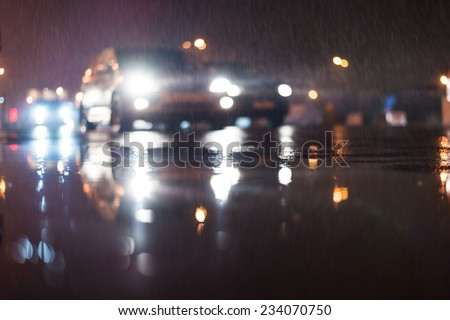 City night lights, car rides at the rain through the night city - stock photo