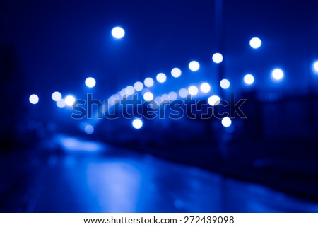 City night lights, road bridge with the lights in the fog after rain. Defocused image, image in the blue toning - stock photo