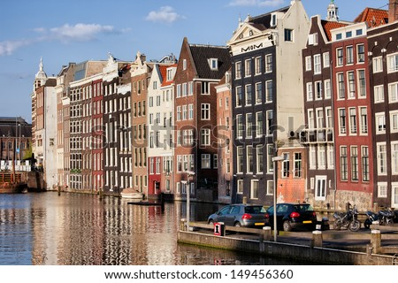 City of Amsterdam at sunset, picturesque historical row houses by the canal, North Holland, Netherlands.