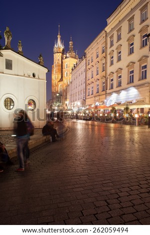City of Krakow by night in Poland. Main Square in the Old Town, Church of St. Wojciech on the left, St Mary Basilica at the far end. - stock photo