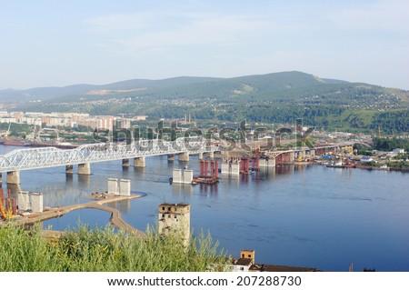 City of Krasnoyarsk (Siberia, Russia). The 4-th Road Bridge building site across the Yenisei river. Industrial cityscape. Summer day, July 22, 2014.   - stock photo