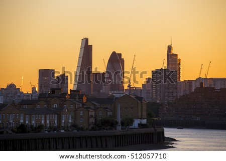 City of London view at sunset, yellow sky, last lights, silhouette of London.