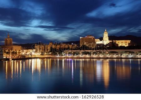 City of Malaga illuminated at dusk. Andalusia, Spain - stock photo