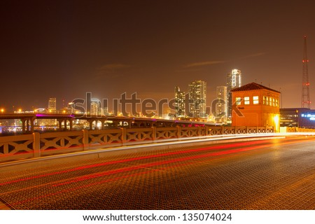 City of Miami Florida, colorful night panorama of downtown business and residential buildings and bridge - stock photo