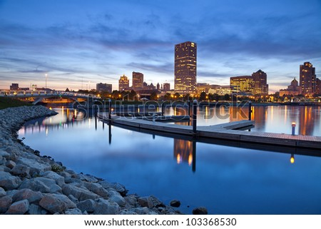 City of Milwaukee skyline. Image of the Milwaukee skyline at twilight with city reflection in lake Michigan and harbor pier. - stock photo