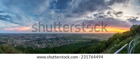 City of Nitra from Above at Sunset with Plants and Railings in Foreground as Seen from Zobor Mountain - stock photo