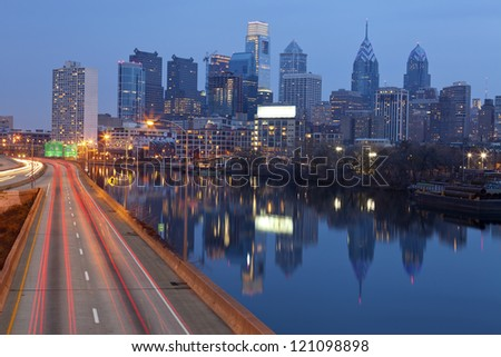 City of Philadelphia. Image of Philadelphia skyline, Schuylkill River and busy highway leading in to the city during sunset. - stock photo