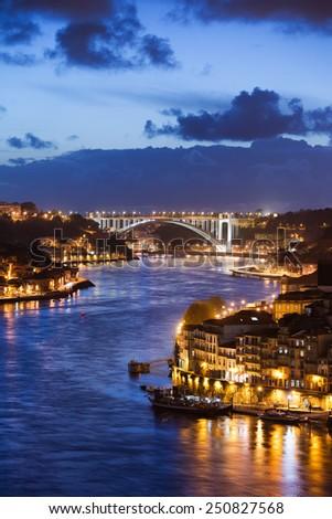 City of Porto and Gaia at night by the Douro river in Portugal, Arrabida Bridge at the far end. - stock photo