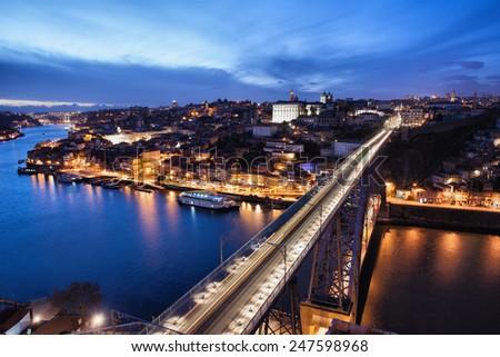 City of Porto at night in Portugal and Dom Luis I Bridge over Douro river. - stock photo