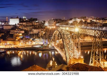 City of Porto in Portugal by night, illuminated Ponte Luiz I Bridge over Douro river, historic city centre. - stock photo