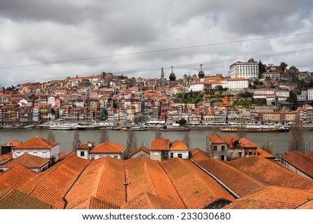 City of Porto in Portugal, view over wine cellars rooftops of Vila Nova de Gaia towards historic city centre along Douro river. - stock photo