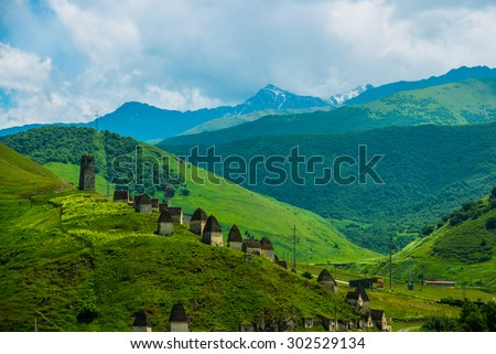City of the dead.Stone ancestral tombs on the hill with mountains in the background, inside the bone. The Caucasus.Russia. - stock photo