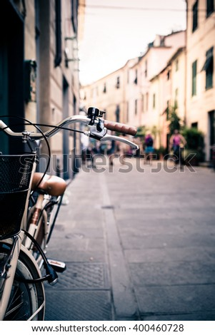 City old bicycle handlebar and basket over blurred street background with people walking. Vintage retro style bike with bokeh copy space. - stock photo