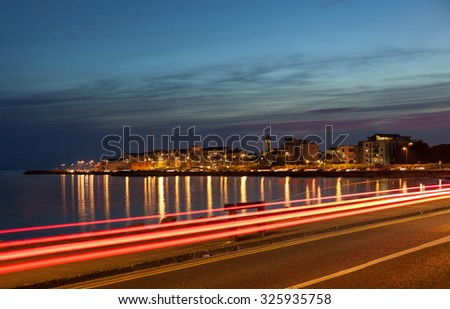 City on the bank of ocean bay and light trails at night. Salthill, Galway