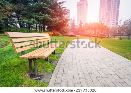 city park after rain ,bench and pedestrian path  - stock photo