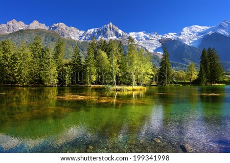 City park in the Alpine resort of Chamonix. Lake with cold water surrounded by trees and snow-capped mountains - stock photo