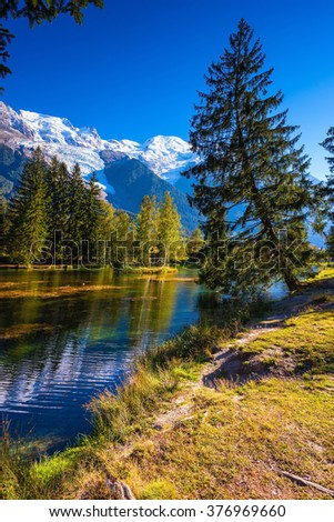 City Park is illuminated by the setting sun. The lake reflected the snow-capped Alps. The mountain resort of Chamonix - stock photo