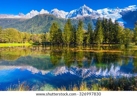 City Park is illuminated by the setting sun. The mountain resort of Chamonix, Haute-Savoie. The lake reflected the snow-capped Alps and evergreen spruce - stock photo