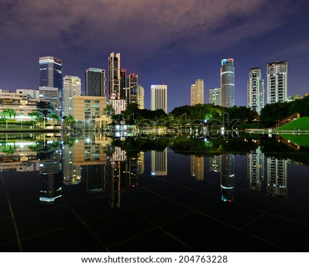 City park with modern buildings in Kuala Lumpur at night reflection in water