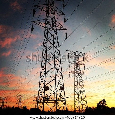 City power lines in the foreground with a colorful sunrise in the background.