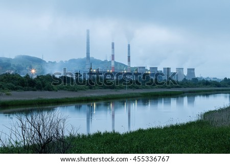City power plant on the river bank at sunrise in fog