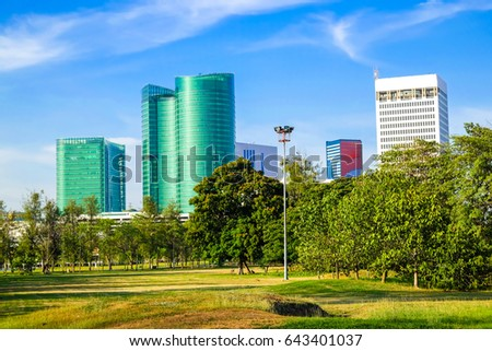 City public park green grass background under blue sky with downtown skyline
