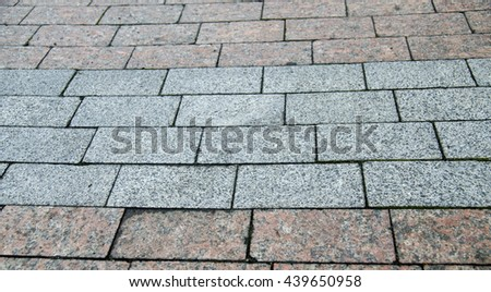 City road pavement made of bricks and stones, road texture in detail - stock photo