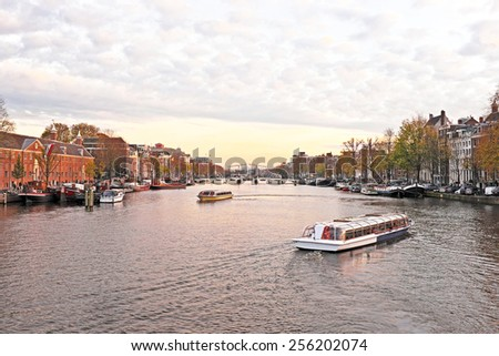 City scenic from Amsterdam in the Netherlands at the river Amstel at twilight - stock photo
