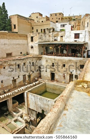 City skyline and view of rooftops, drying hides and dye pots at a leather tannery at the Terrace de Tanneurs in the ancient medina, Fes el Bali, in Fez, Morocco