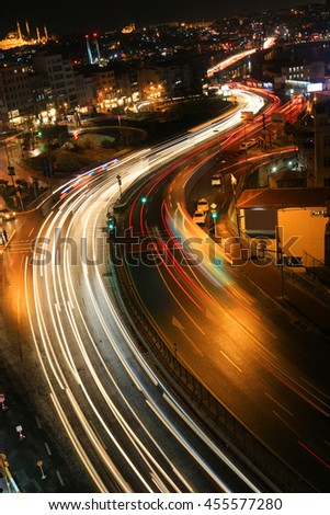 City skyline at night of Istanbul Turkey and the Golden Horn Bosphorus River  viewing car lights crossing bridge - stock photo