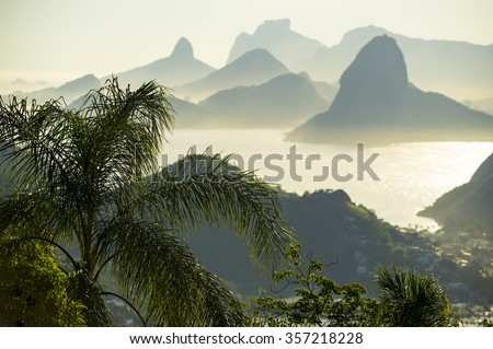 City skyline scenic overlook of Rio de Janeiro, Brazil with Niteroi, Guanabara Bay, and Sugarloaf Mountain through palm fronds - stock photo