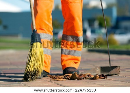 City street male or female sweeper cleaning pavement with broom tool - stock photo