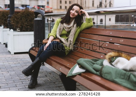 City stylish portrait of beautiful woman posing at the street, nice fall autumn day. Wearing bright green casual sweater. - stock photo