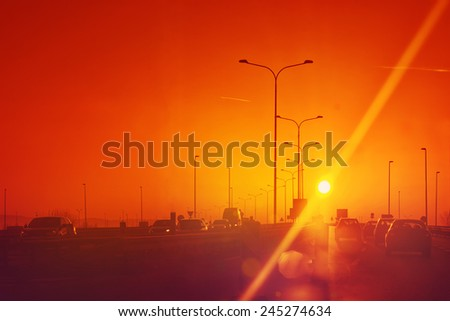 City Traffic in Sunset, Cars driving on Roadway, Toned image with Sun Flare - stock photo