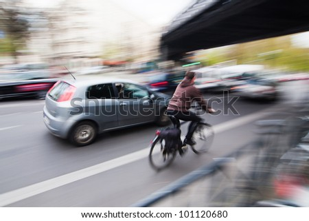 city traffic with a cyclist and cars in motion blur