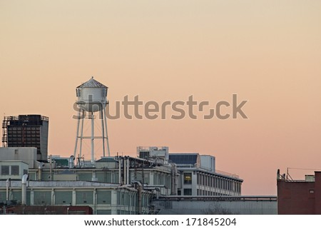 City water tower against a sunset sky