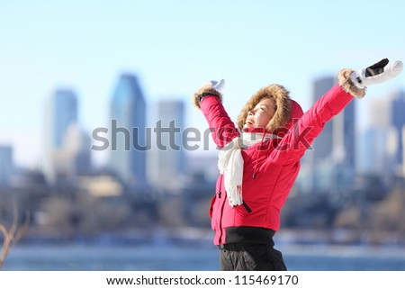 City winter woman happy standing excited and elated with arms raised in joy. Beautiful young woman and Montreal City skyline, Quebec, Canada. - stock photo