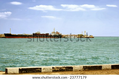 City Yalta. The peninsula of Crimea. Ukraine. Sunny day transport ship is far from the pier. Adjacent to the small boat. Even farther on the edge of the pier stands a lighthouse.