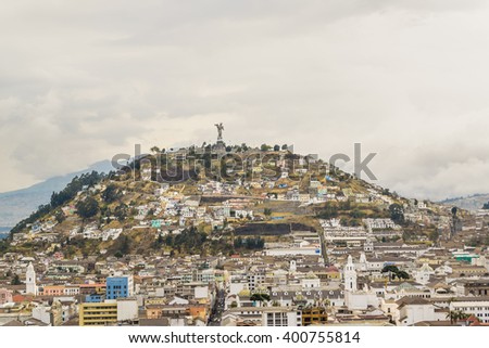 Cityscape aerial view of famous panecillo hill in Quito city from the top of San Juan Basilica church. - stock photo