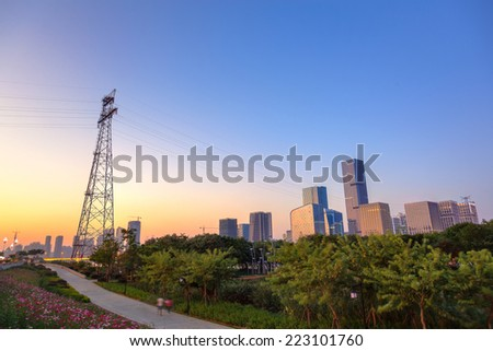 Cityscape at dusk including a large vertical steel tower supporting high-tension wires through beautiful leisure park   and  the skyscapers,Fuzhou,China. - stock photo