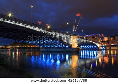 Cityscape: illuminated bridge over the Rhone river in Lyon at dusk. - stock photo
