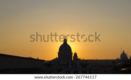 Cityscape in Rome at dusk with sun back the cupola