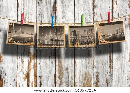 Cityscape monochrome photo hanging on clothesline on wood background. Bangkok, Thailand. - stock photo