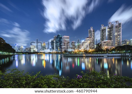 Cityscape of Bangkok at twilight with moving clouds and reflection of modern building
