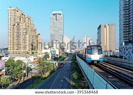 Cityscape of Bangkok, the fast developing capital city of Thailand, with view of a BTS skytrain traveling on an elevated metro system between high rise skyscrapers in downtown on a beautiful sunny day - stock photo