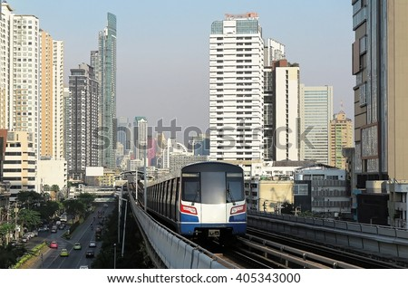 Cityscape of Bangkok, the fast developing capital city of Thailand, with view of a BTS skytrain traveling on an elevated rail system between high rise skyscrapers in downtown on a beautiful sunny day